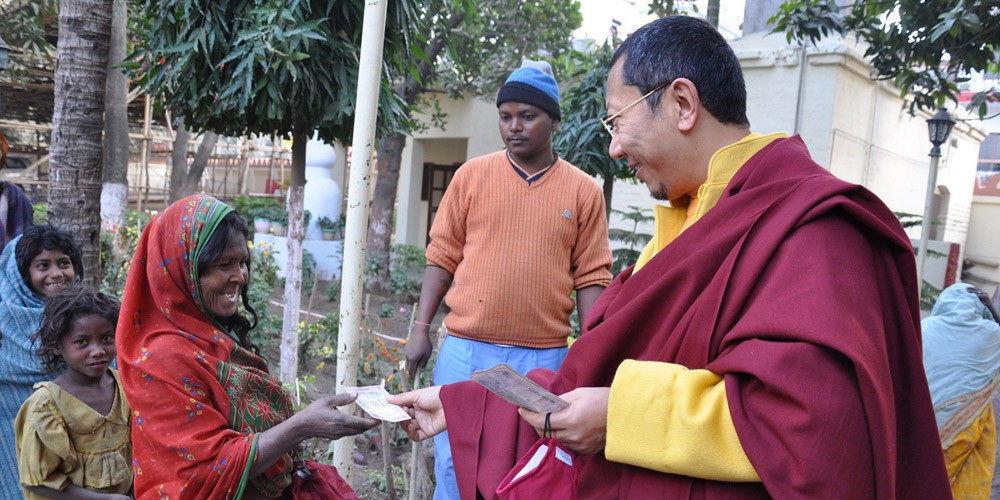 Distributing alms with students in Bodhgaya, India.